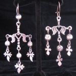 These earrings come from the town of Yalalag in the state of Oaxaca, Mexico. This design dates from colonial times when the Spanish ruled Mexico. The symbolism of the Yalalag cross refers to the crucifixion with the large cross representing Jesus and the three smaller crosses for the three men sentenced to death on the mountain with Jesus.